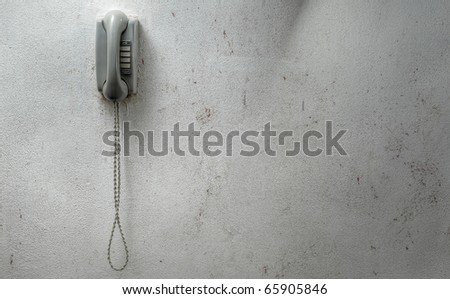 vintage phone mounted against a dirty wall - stock photo