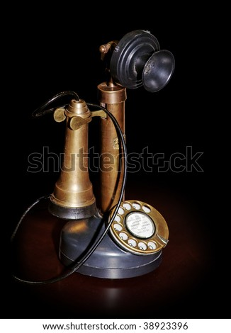 Vintage phone on table isolated on black (pure black edges on picture) with clipping path - stock photo