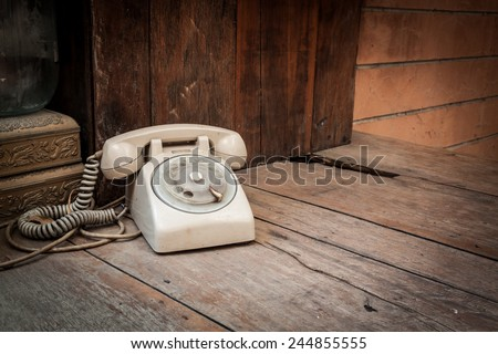 Vintage phone on wood background in vignetted - stock photo
