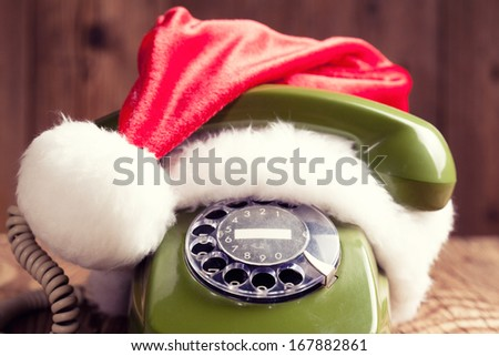 vintage phone with Santa's hat on wooden background - stock photo
