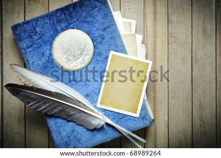 Vintage photo album empty photo frames and quill feathers on  a wooden table - stock photo