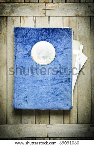 Vintage photo album in a blue plush cover, on an old wooden table - stock photo