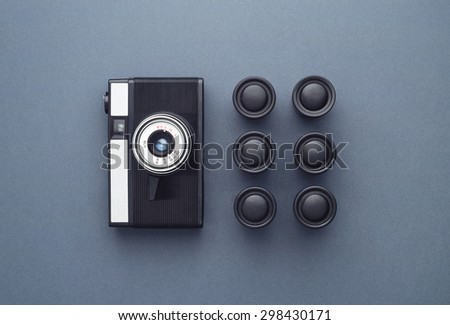 Vintage Photo Camera and photo film rolls well organized over dark blue background, above view - stock photo