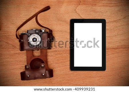 Vintage photo camera in cover and digital tablet with blank screen on a wooden table. View from above - stock photo