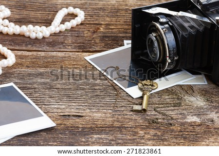vintage  photo camera on pile of old blank instant photos on wooden table  - stock photo
