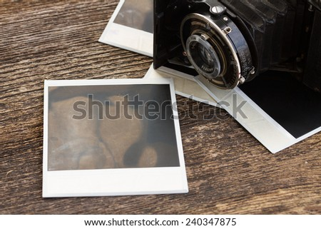 vintage  photo camera on pile of old instant photos  - stock photo