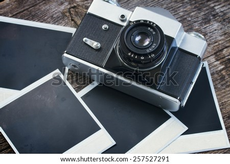 vintage  photo camera on pile of old instant photos  on wooden table, retro toned - stock photo