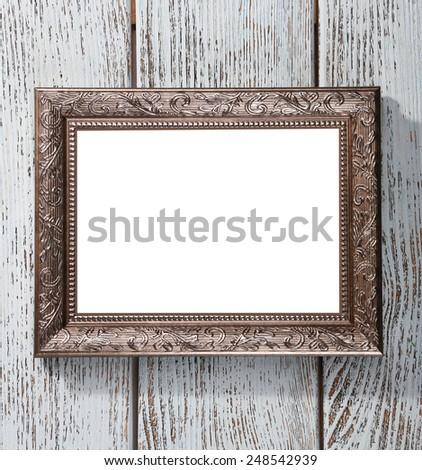 Vintage photo frame on color wooden background - stock photo