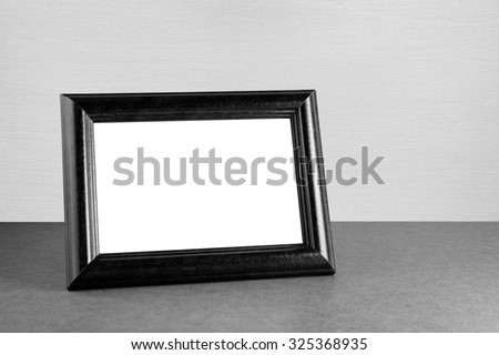 Vintage photo frame on table in black and white - stock photo