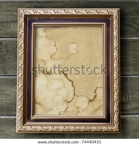 Vintage photo frame on weathered wooden wall - stock photo