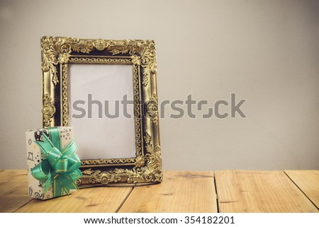 Vintage photo frame with gift box on wooden table over grunge background, Still life style - stock photo