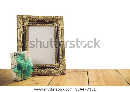 Vintage photo frame with gift box on wooden table over white background, Still life style - stock photo