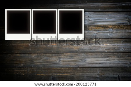 Vintage photo frames on wooden board background texture
