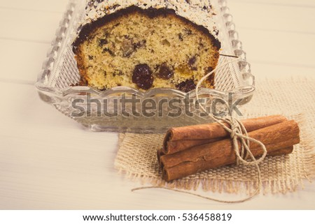 Vintage photo, Fresh baked homemade fruitcake and cinnamon sticks on boards, delicious dessert