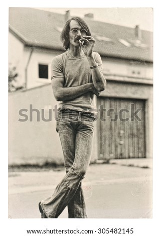 Vintage photo from young fashion smoking man wearing typical 1970s clothing. Retro picture with original film grain and scratches. - stock photo