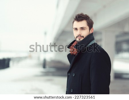 Vintage photo handsome stylish bearded brunette man in black coat looks away outdoors  - stock photo