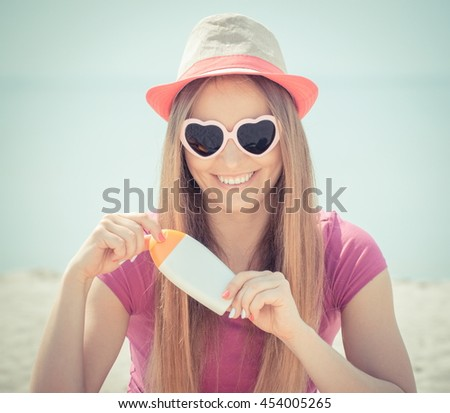Vintage photo, Happy girl wearing straw hat and sunglasses in shape of heart on seaside and holding sun lotion, sun protection on beach - stock photo