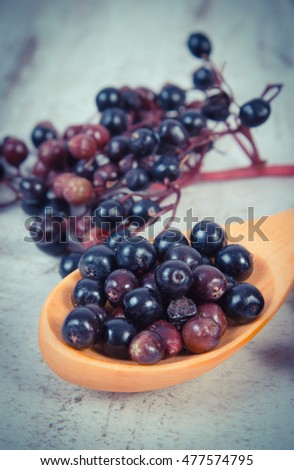 Vintage photo, Heap of elderberry on wooden spoon and bunch of berry on old rustic board, healthy food, nutrition and alternative medicine