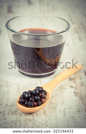Vintage photo, Heap of fresh elderberry on wooden spoon and glass of elderberry juice on old rustic wooden background, healthy nutrition, alternative medicine and therapy - stock photo