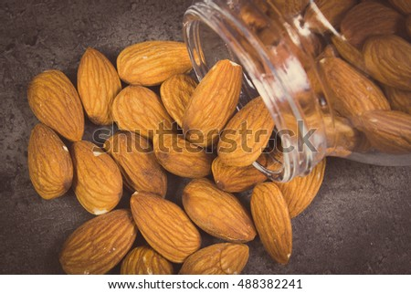 Vintage photo, Heap of fresh healthy almonds spilling out of glass jar on structure of concrete, concept of healthy nutrition