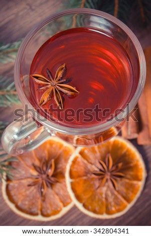 Vintage photo, Mulled wine for christmas or winter evening on wooden surface plank, spruce branches and spices, cinnamon anise dried orange - stock photo