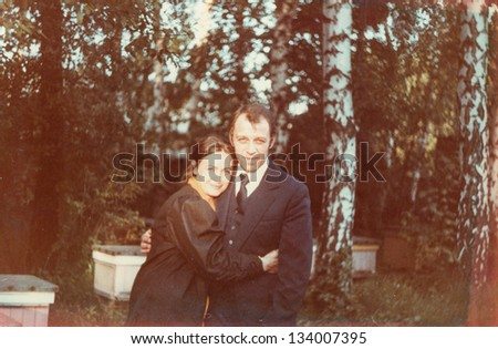 Vintage photo of a couple hugging outdoor (seventies) - stock photo