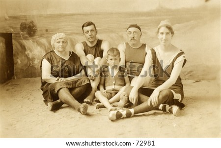 Vintage photo of a family in bathing costumes in front of painted background - stock photo