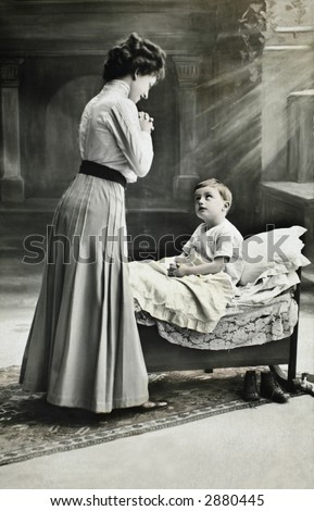 Vintage photo of a mother gazing at her young son in bed. - stock photo
