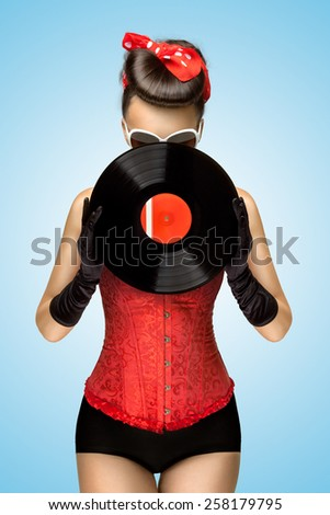 Vintage photo of a retro pinup girl, dressed in a red sexy corset, hiding behind retro vinyl on blue background. - stock photo