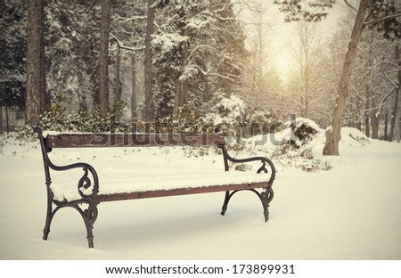 Vintage photo of a snowy bench in the park - stock photo