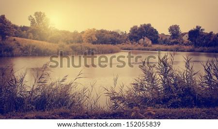 Vintage photo of autumn scene with lake - stock photo