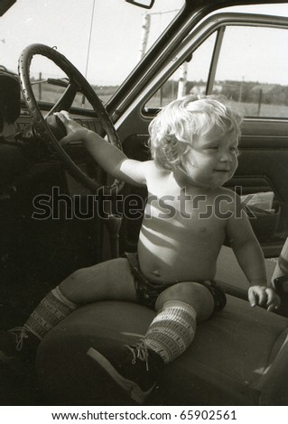 Vintage photo of baby girl in a car - stock photo
