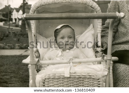 Vintage photo of baby girl in pram (fifties) - stock photo