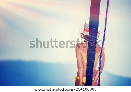 Vintage photo of beautiful female tanning on the yacht, active lifestyle, back side of sexy tanned woman body, luxury sea cruise, traveling and tourism concept  - stock photo