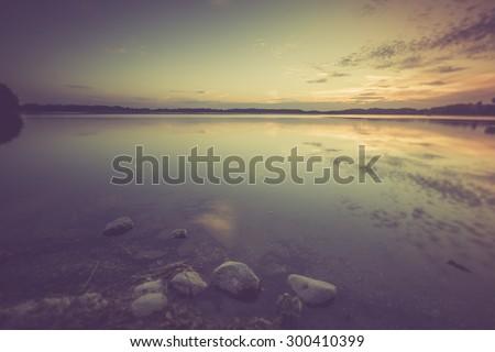 Vintage photo of beautiful lake sunset. Polish lake in Mazury lake district. Polish lake landscape - stock photo
