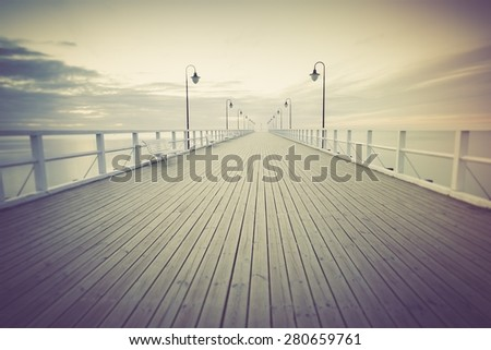 Vintage photo of beautiful long exposure seascape with wooden pier. Pier in Orlowo, Gdynia in Poland. - stock photo