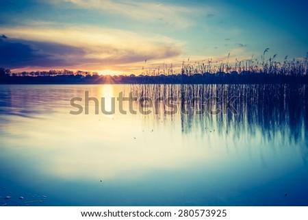Vintage photo of beautiful sunset over calm lake. Mazury lake district landscape. - stock photo