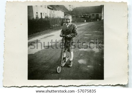 Vintage photo of boy with a scooter - stock photo
