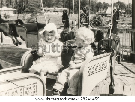 Vintage photo of brother and sister on carousel (eighties) - stock photo
