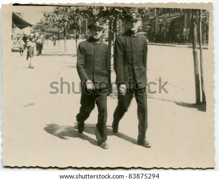 Vintage photo of brothers in school uniforms walking on the street (thirties) - stock photo