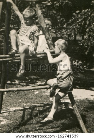 Vintage photo of brothers playing outdoor, fifties - stock photo