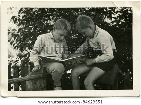 Vintage photo of brothers reading a book (fifties) - stock photo