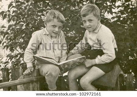 Vintage photo of brothers reading a book (sixties) - stock photo