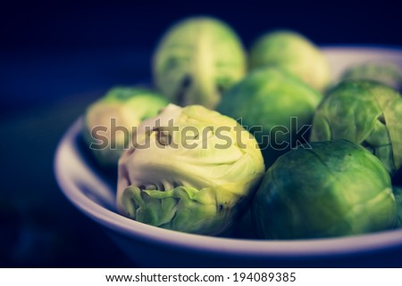 vintage photo of brussels sprouts on wood table - stock photo