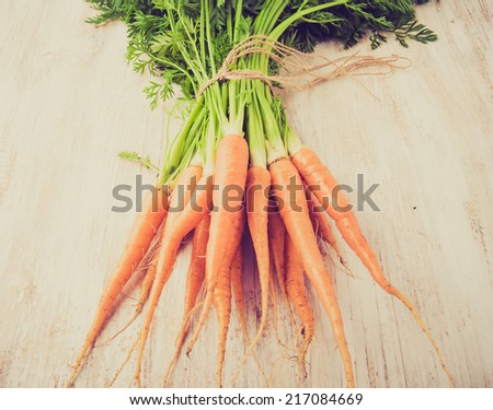 vintage photo of bunch of fresh carrots on a wooden table - stock photo