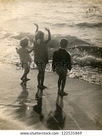 Vintage photo of children at seaside, fifties - stock photo