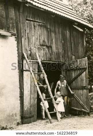 Vintage photo of children playing in barn, fifties - stock photo