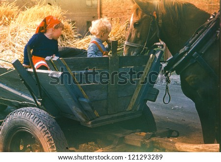 Vintage photo of children playing in horse-drawn wagon (early eighties) - stock photo