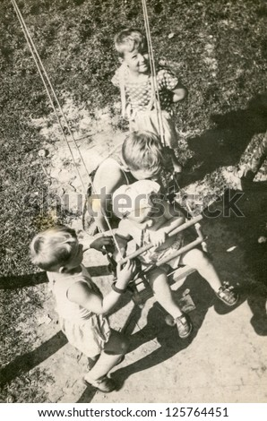 Vintage photo of children playing outdoor (early fifties) - stock photo