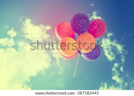 Vintage photo of colorful balloons on blue sky. Concept of love in summer, valentine, wedding and honeymoon - stock photo